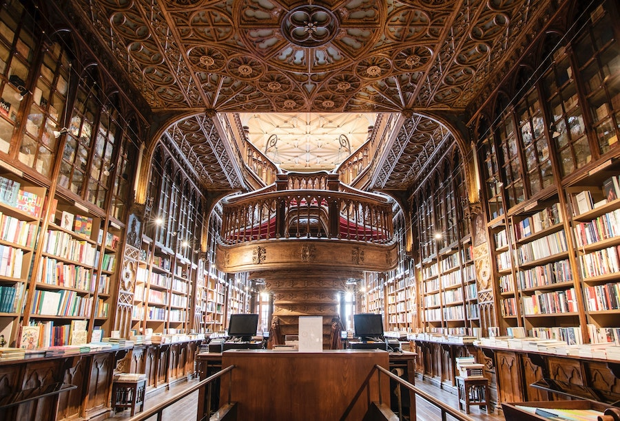 Covered bookshelves stretch floor to ceiling with ornate wooden buttresses and crown molding.