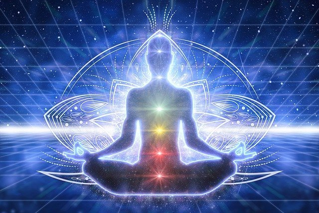 A person meditating on their chakras as illustrated by the chakra system illuminated within a human outline.